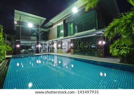 Modern house with swimming pool at night - stock photo