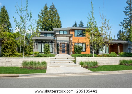 Modern house with wood trim exterior and beautiful landscaping. Home exterior design. - stock photo
