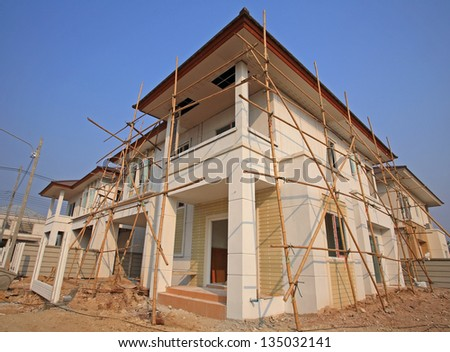 Modern houses with wooden scaffold under construction - stock photo
