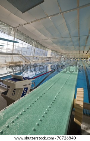 Modern indoor swimming pool with green spring board - stock photo