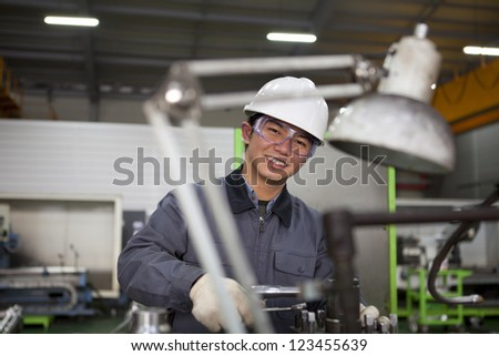 modern industrial machine operator working in factory - stock photo