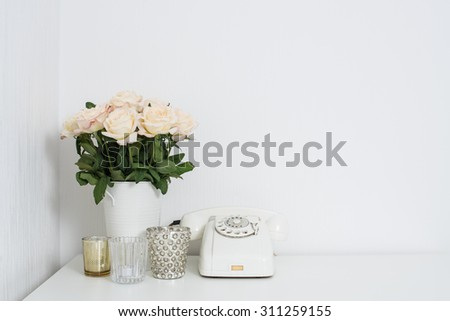 Modern interior decor with vintage details: white rotary phone and fresh flowers on a table. Clean white room in real apartment.