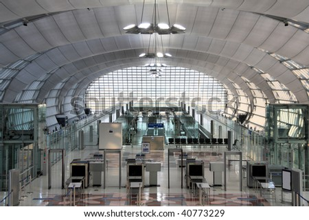 Modern interior of famous Bangkok Suvarnabhumi International Airport. Security control machines and departures area. - stock photo