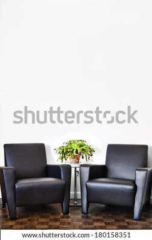 Modern Interior Room and white wall with space for your text. Two luxurious couch and glass table with accessories of your choice. - stock photo