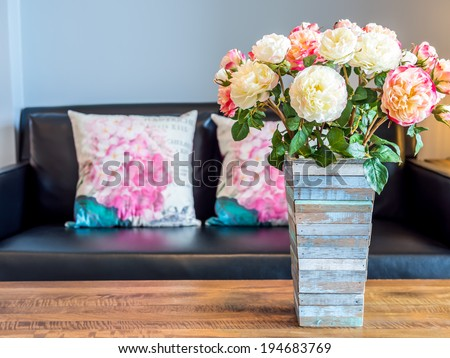Modern interior room decorated with artificial flowers in rustic wooden vase - stock photo