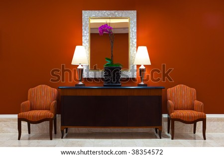 Modern interior with a luxurious dresser with classic lamps, plant and a mirror in a hallway with two classic chairs. - stock photo