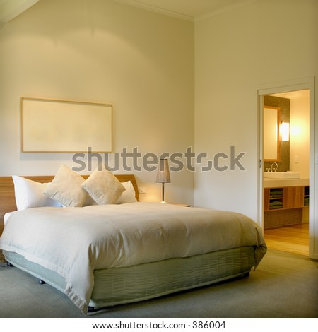 Modern interior with King size bed and bathroom in background