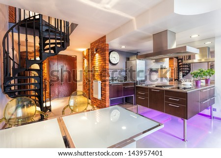 Modern interior with kitchen, dining room and a staircase - stock photo