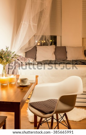 Modern interior with white chair, wood table and bed with decorative cushions