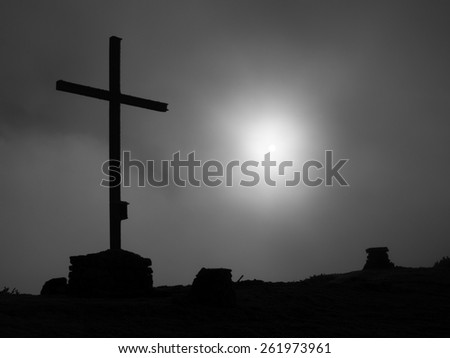 Modern iron cross at a mountain top in Alps. The memorial to victims of mountains on  a mountain peak as typical in the Alps.  - stock photo
