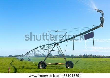 modern irrigation machine working in grassland in blue sky - stock photo