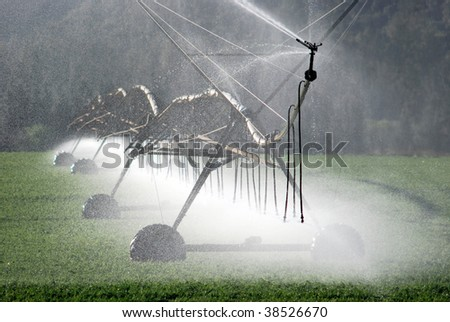 Modern irrigation pivot watering a farm field - stock photo