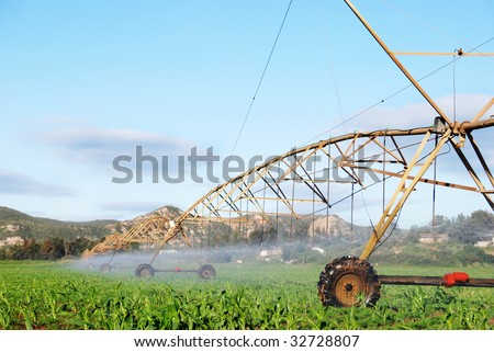 Modern irrigation system watering a farm field - stock photo