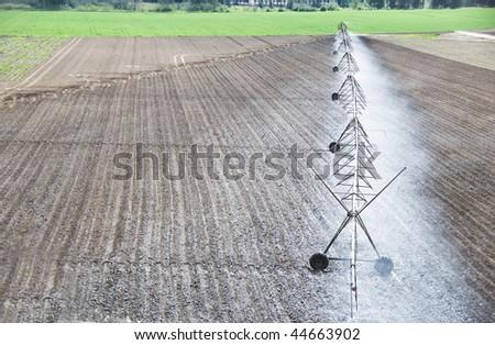Modern irrigation system watering a farm field - stock photo