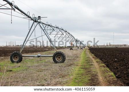 Modern irrigation tool. Crop Irrigation using the center pivot sprinkler system - stock photo