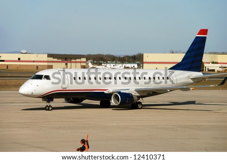 Modern jet airplane approaching terminal gate - stock photo