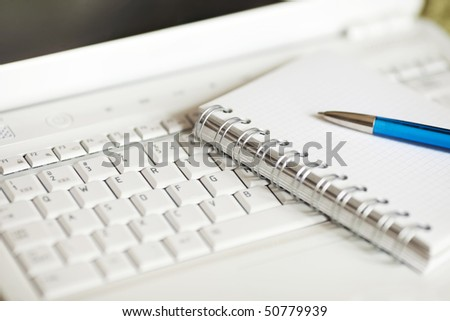 Modern journalist tools, white laptop, notebook and a pen. Shallow depth of field, focus on binding - stock photo