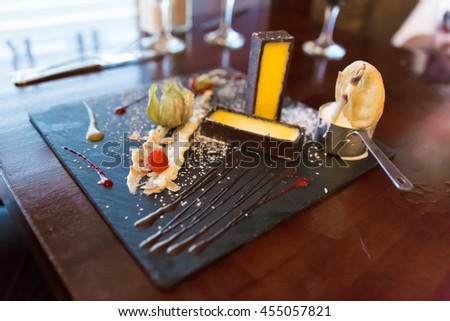 Modern key lime pie with ice cream served on a black square plate with a cookie and chocolate sauce - stock photo
