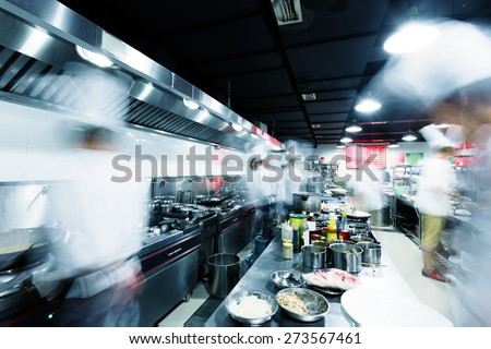 Modern kitchen and busy chefs in hotel - stock photo
