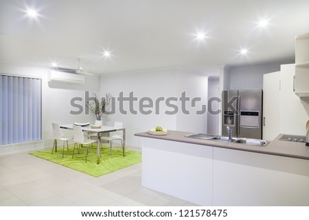Modern kitchen and dining area in modern suburban house - stock photo