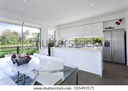 Modern kitchen and dining room with stainless steel appliances in Australian mansion - stock photo