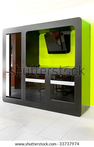 Modern kitchen appliances in black over green wall - stock photo