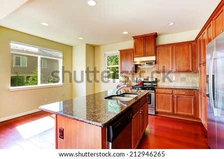 Modern kitchen cabinets with ss-appliances and kitchen island with built-in sink and granite top - stock photo