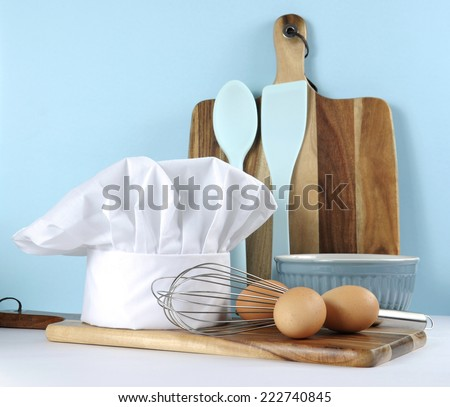 Modern kitchen cooking kitchenware and chef's hat with mixing bowl, whisk, chopping boards and eggs on a pale aqua blue and white background. - stock photo