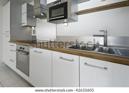 modern kitchen counter with built in appliances and hard wood worktop - stock photo