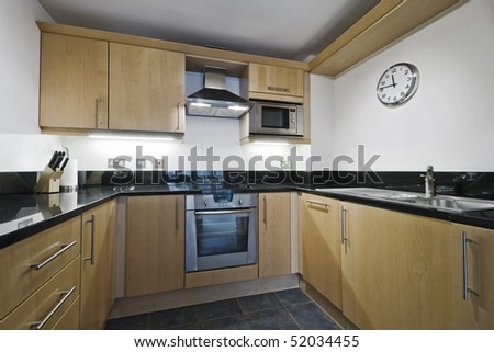 modern kitchen counter with hard wood finish and granite worktop - stock photo