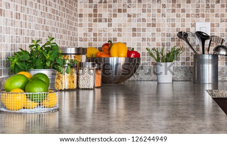 Modern kitchen countertop with food ingredients and green herbs. - stock photo