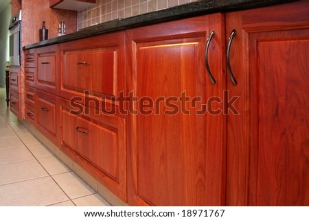 Modern kitchen cupborads and drawers made in rosewood - stock photo