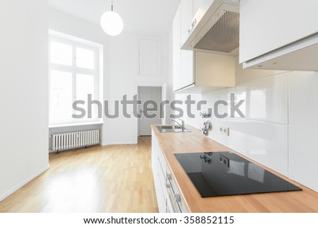 modern kitchen, fresh renovated flat - white kitchen with wooden floor - stock photo