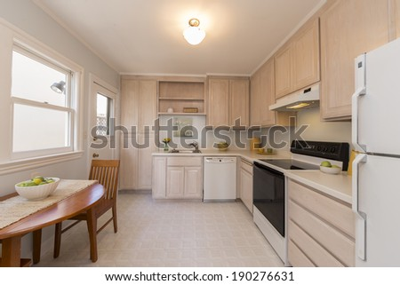 Modern kitchen in beige with sitting area  - stock photo
