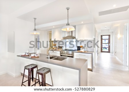 Modern kitchen interior at day time with a way to go to an outside door on the tile floor, there are plastic chairs near the counter
