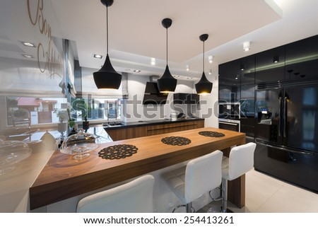 Modern kitchen interior design in black and white style with wooden counter - stock photo