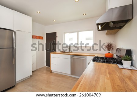 Modern kitchen interior in with white cabinets and amazing wooden counter top. Amazing Design concept. - stock photo