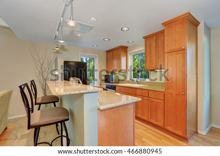 Modern kitchen interior with bar and stools. Maple kitchen cabinets and granite counter tops. Northwest, USA