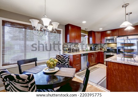 Modern kitchen interior with bright wooden cabinets and steel appliances. Mosaic back splash trim blend perfectly with granite tops. Black round dining table with black and zebra chairs - stock photo
