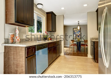 Modern kitchen interior with dark brown storage cabinets with granite counter tops and new tile floor. View of dining area