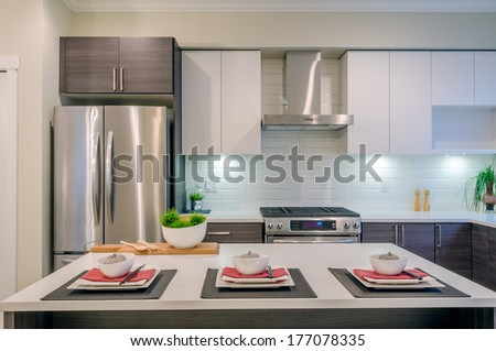 Modern kitchen interior with island and cabinets in a luxury house set for dinner - stock photo