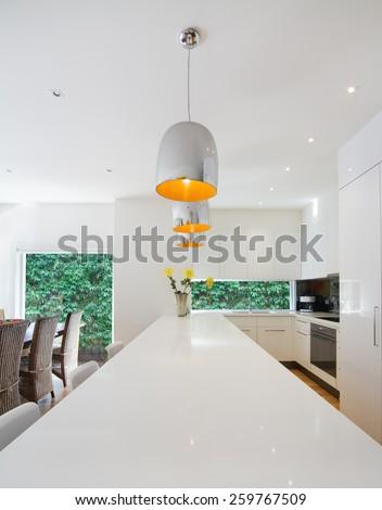 Modern kitchen renovation with hanging chrome pendant light - stock photo