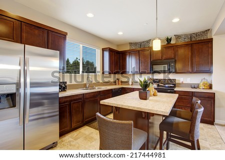 Modern kitchen room with kitchen island and stools.  Dark brown cabinets, steel appliances and tile floor - stock photo