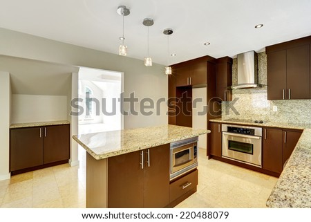 Modern kitchen room with matte brown cabinets, shiny granite tops, steel stove with hood and granite back splash - stock photo