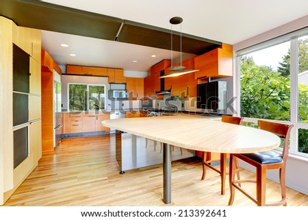 Modern kitchen room with orange cabinets and dining table with stools