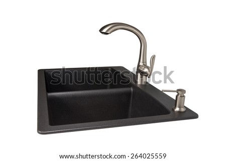Modern kitchen sink made of black synthetic granite with brushed stainless steel faucet and soap dispenser.  Isolated on a white background.  Viewed from the side.  Contemporary living and design. - stock photo