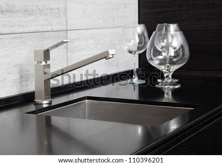 Modern kitchen sink with metal tap and black marble