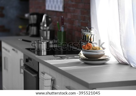 Modern kitchen table with electric stove beside the window - stock photo