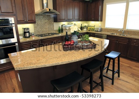 Modern kitchen with a hardwood floor and granite island.