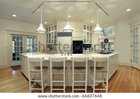 Modern kitchen with breakfast bar and cream colored cabinetry - stock photo